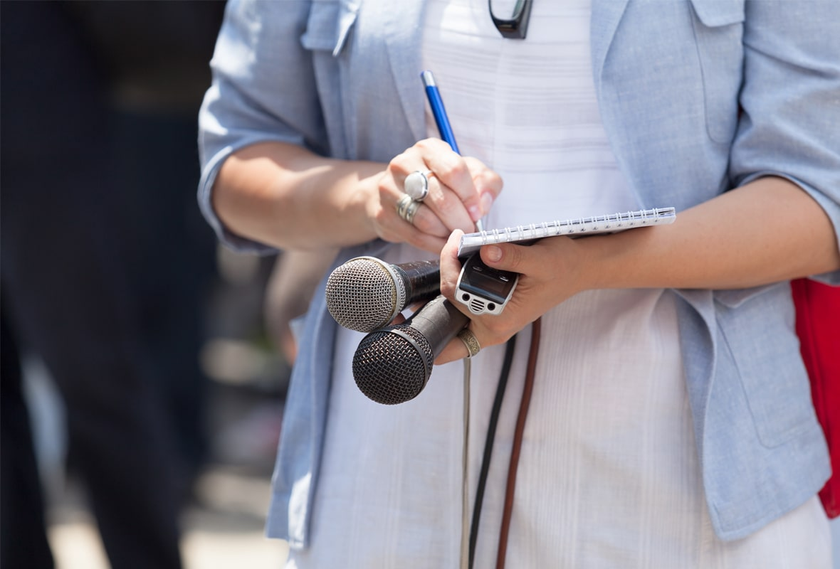 Woman holding two microphones and writing on a notepad