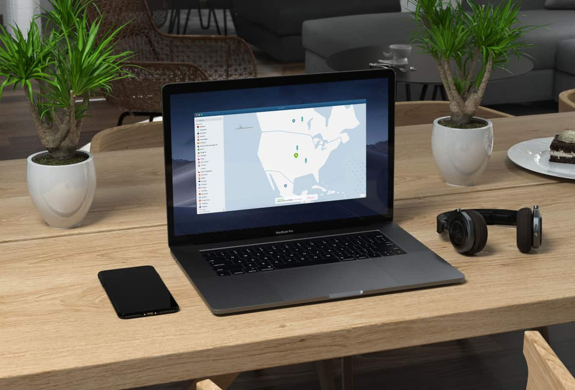 MacBook with NordVPN app on the screen sat on top of a wooden table