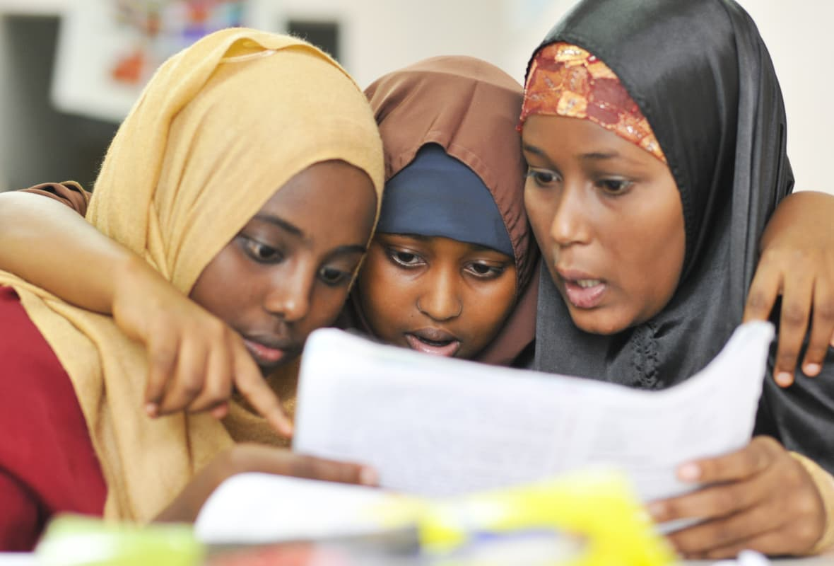 Three Somalian Citziens Look at School Paper