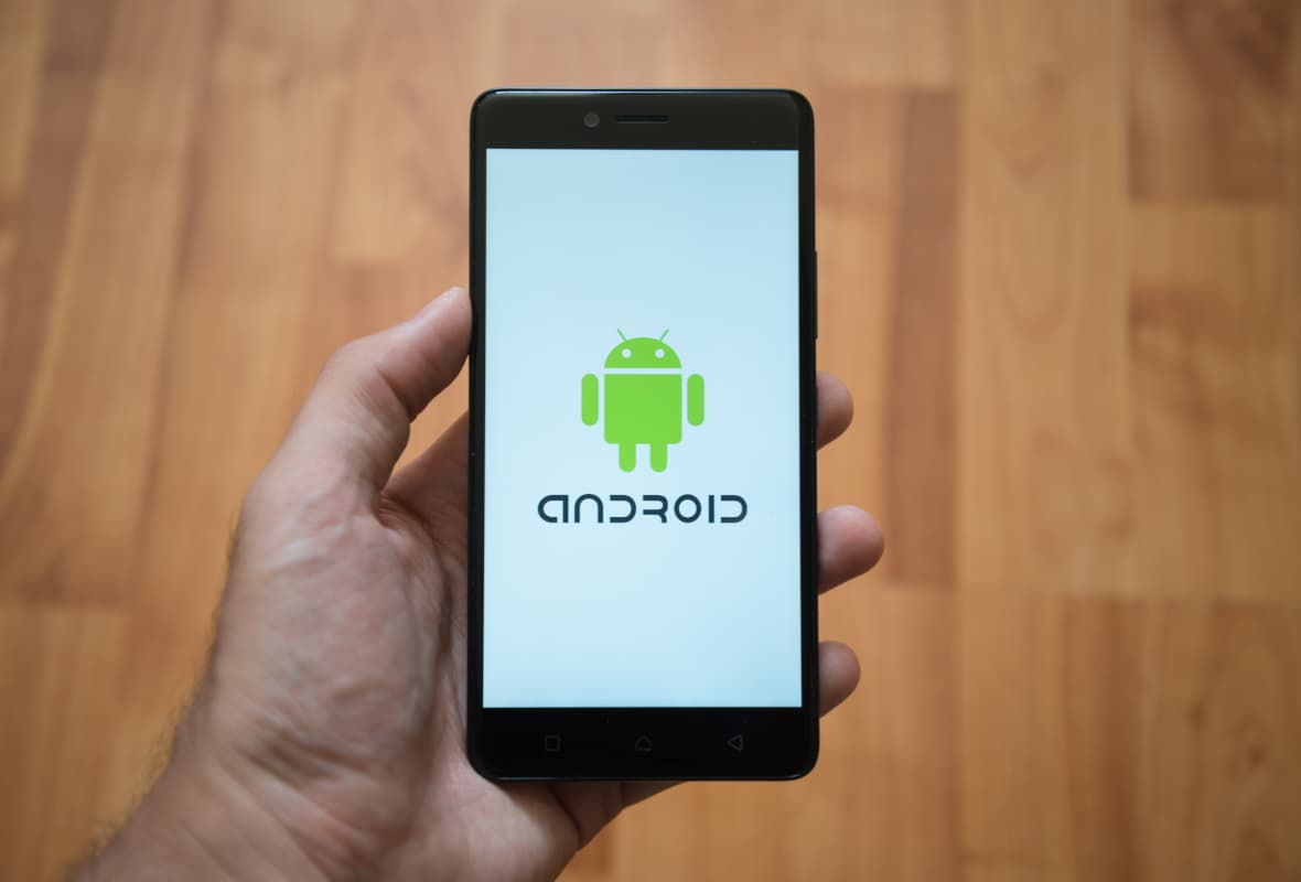 Person Holding Android Mobile Phone With Android Logo On Screen