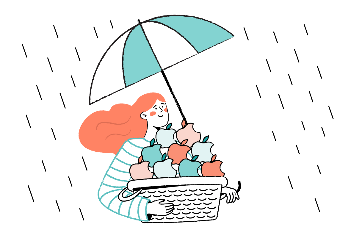 Woman holding a basket of apples and an umbrella in the other hand
