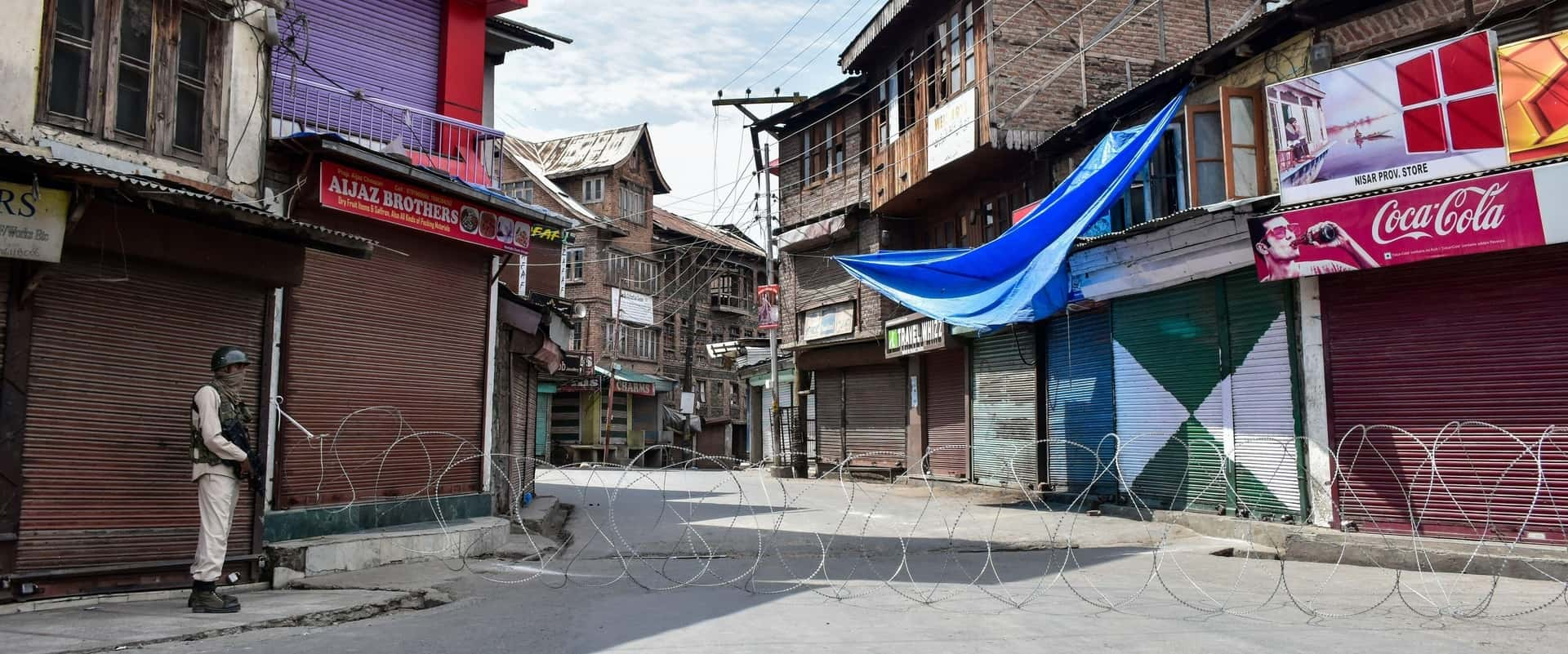 Soldier standing guard in a Kashmir street divided by barbed wire in Aug 2020 on the anniversary of the internet shutdown starting